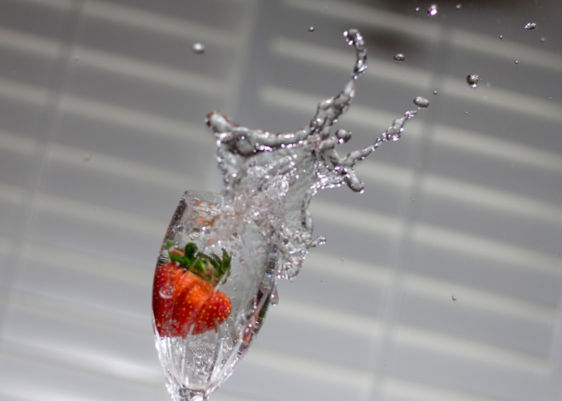 Red Strawberry Drops into Goblet